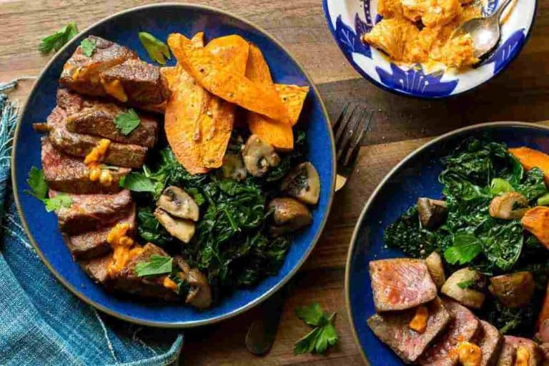 Steak and sweet potato fries with kale and mushrooms